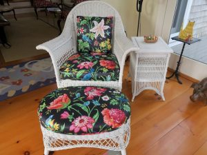 Antique Wicker Chair and Matching Foot Stool | Upholstered in a Schumacher Chintz Floral Print | Upholstered by Cape Cod Upholstery Shop | Located in South Dennis, MA