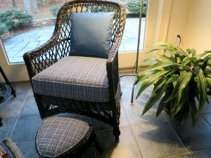 Black wicker chair and foot stool with removable seat cushion and back pillow | Upholstered in a Stout Fabrics and Greenhouse Fabrics stripe and solid | Upholstered by Cape Cod Upholstery Shop | Located in South Dennis, MA 02660