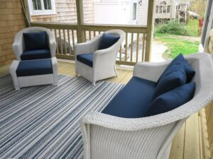 Lloyd Flanders white outdoor wicker chairs, ottoman and love seat | Cushions upholstered with Sunbrella Spectrum Indigo outdoor fabric | EZ-Dri foam inserts | Upholstered by Cape Cod Upholstery Shop | Located in South Dennis, MA 02660