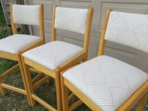 Side view of matching wood bar stools   Upholstered in a geometric pattern fabric   Upholstered by Cape Cod Upholstery Shop   Located in South Dennis, MA 02660